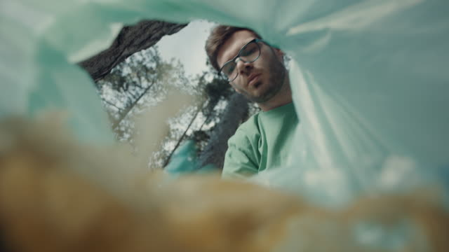vídeos de stock e filmes b-roll de man putting trash in plastic bag - levantar