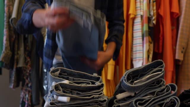 vídeos de stock e filmes b-roll de man putting trousers - calças de ganga