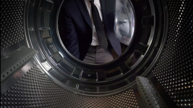 pov man putting uk pounds into a washing machine - launderette stock videos and b-roll footage