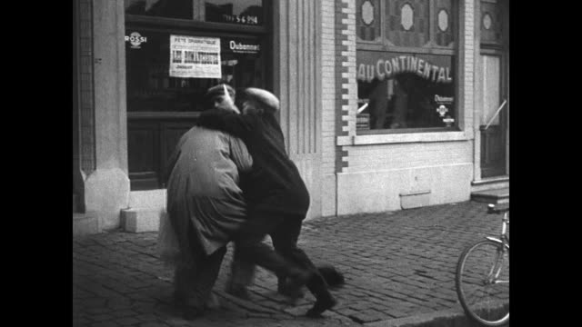 man putting up anti-degrelle poster 'degrelle serves hitler.' two men attack rexist newsman on street. rexist newsmen handing out papers. vs rex... - belgium stock videos & royalty-free footage