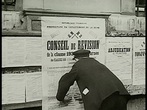 man putting up poster on wall 'conseil de revision' int men looking through boxes of records files ms officers taking packet of papers cu filling in... - anno 1938 video stock e b–roll