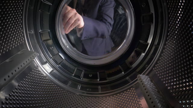 pov man putting us dollars into a washing machine - laundry stock videos & royalty-free footage