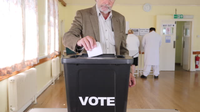 4k: man putting vote in ballot box at the elections - voting at polling station / place - voting booth stock videos and b-roll footage