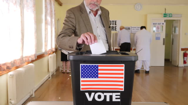 4K: Man Putting Vote in Ballot Box at the USA Election - Voting at Polling Place