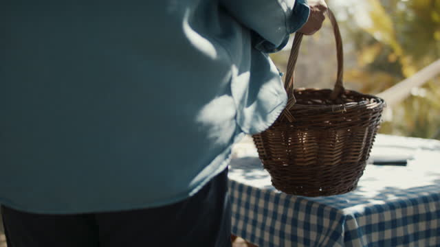 man putting wicker basket on table on sunny day - lunch stock videos & royalty-free footage