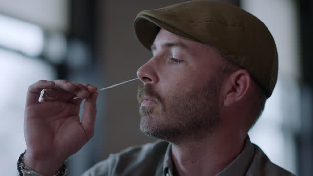 stockvideo's en b-roll-footage met cu man quickly swabs his nose with a cotton swab - testkit