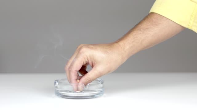 mann hörte mit dem rauchen auf, indem er seine zigarette in den aschenbecher steckte - aschenbecher stock-videos und b-roll-filmmaterial