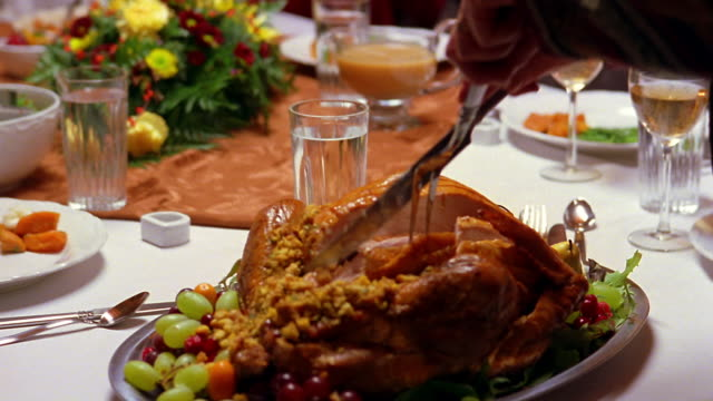 a man raises his plate to accept a piece of turkey at thanksgiving dinner. - thanksgiving stock videos & royalty-free footage