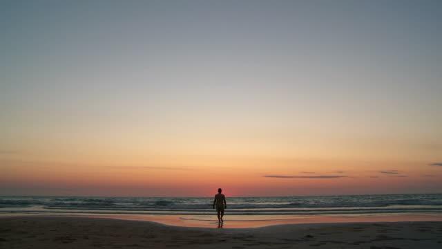 hd: man raising arms on a beach at sunset - western australia bildbanksvideor och videomaterial från bakom kulisserna