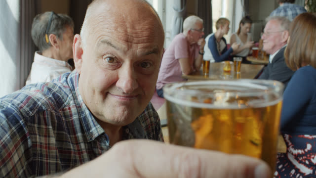 man raising full beer to camera in crowded pub - senior men stock videos & royalty-free footage