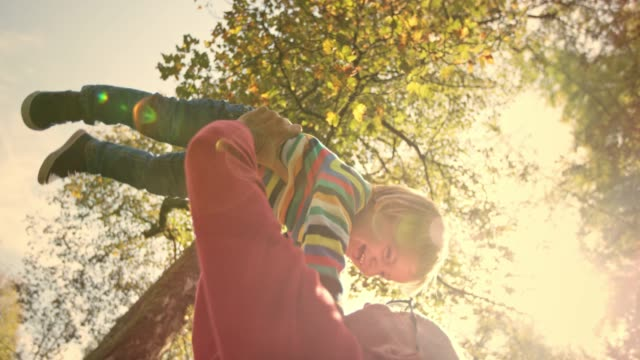 slo mo man raising his small laughing child in the air in the sunny park under a tree - grandchild stock videos & royalty-free footage