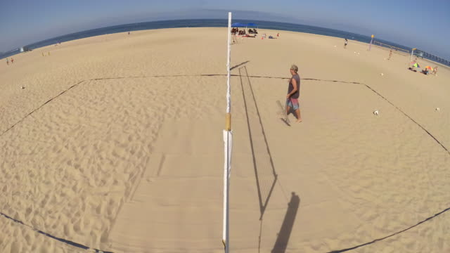 A man rakes a beach volleyball court.