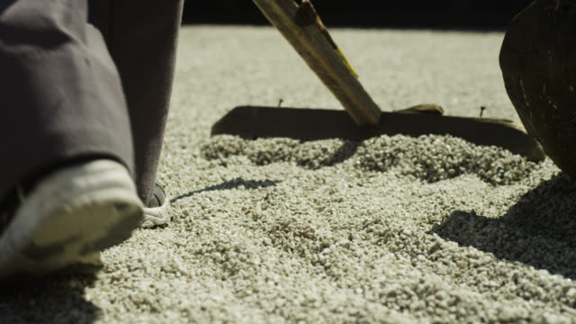 Man rakes gravel in zen garden at Gyokudo art museum.