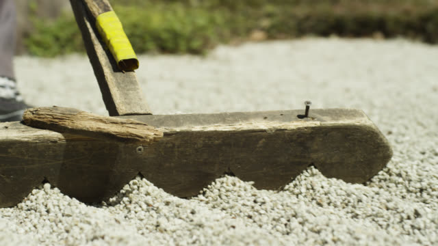 stockvideo's en b-roll-footage met man rakes gravel in zen garden at gyokudo art museum. - grind