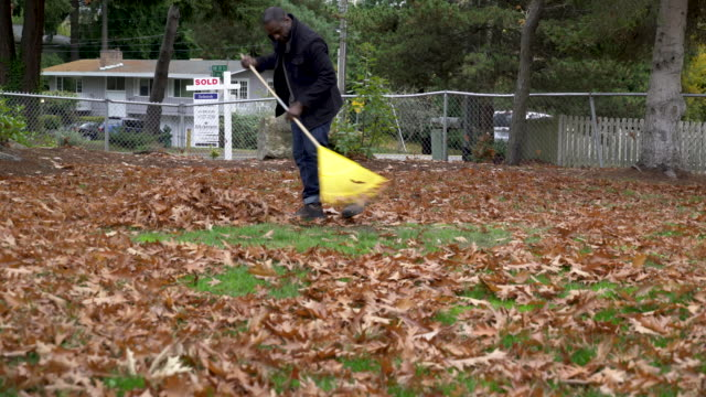 man raking autumn leaves in domestic garden, zooming in. - one mid adult man only stock videos & royalty-free footage