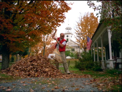 Man raking autumn leaves into large pile in front of house / church in background / Vermont