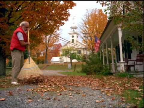 vídeos de stock e filmes b-roll de man raking autumn leaves on lawn in front of house / church in background / vermont - ancinho equipamento de jardinagem