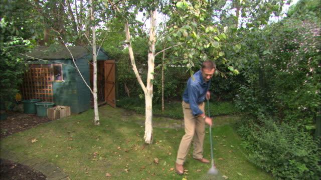 ws man raking leaves near garden shed - endast en medelålders man bildbanksvideor och videomaterial från bakom kulisserna
