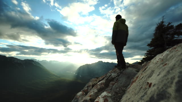 Man reaches summit ridge, looks out to distant mountains