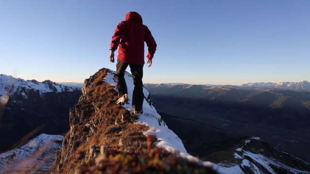 a man reaching the summit after climbing on a snow covered mountain. - ganz oben stock-videos und b-roll-filmmaterial