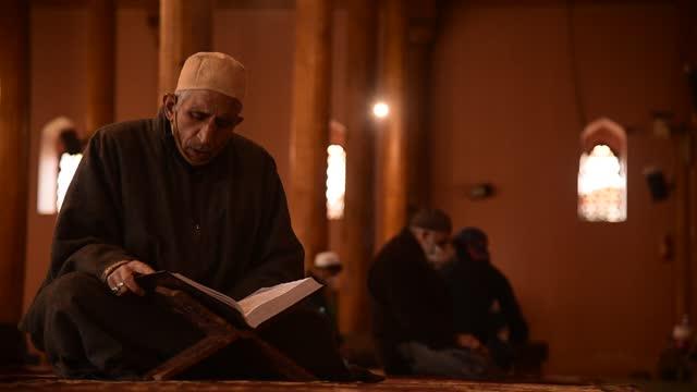 man read qur'an after friday prayers inside jamia masjid in srinagar on 16 april 2021. islam's holiest month ramadan is the period of intense prayer,... - islam stock videos & royalty-free footage