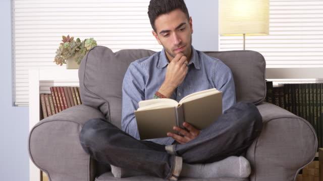man reading a book at home - プエルトリコ人点の映像素材/bロール