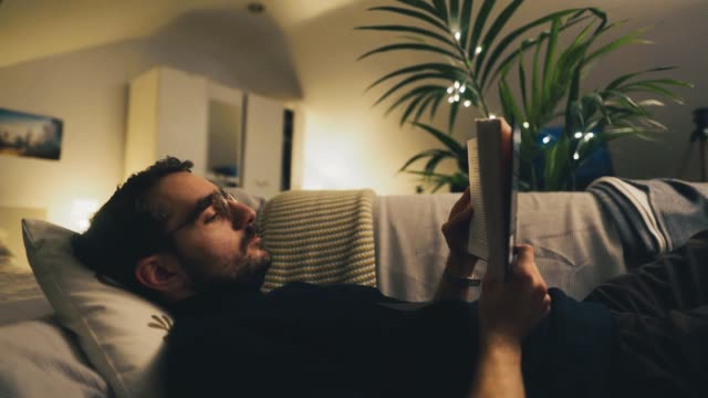 man reading a book in his bedroom - modern manhood stock videos & royalty-free footage