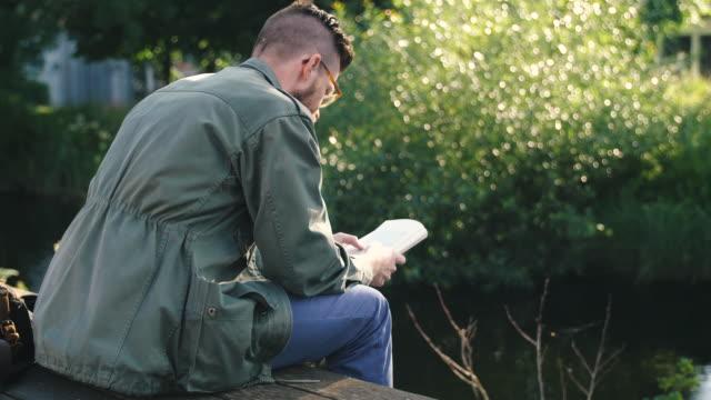 mann liest ein buch - lesebrille stock-videos und b-roll-filmmaterial