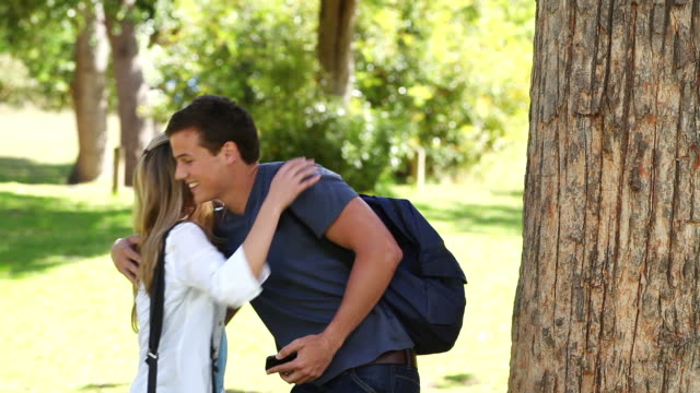 Man reading a text message while leaning against a tree before hugging a woman and laughing