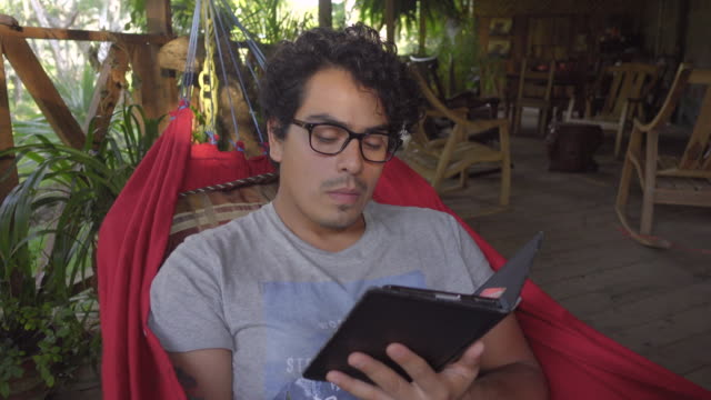 Man reading an e-book in a hammock. Close up. Located in a porch wooden cabin in a tropical country. Cabin Retreat - Brief