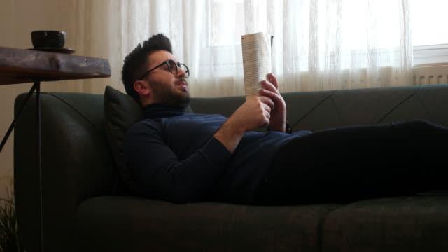 vidéos et rushes de livre de lecture d'homme à la maison - lire