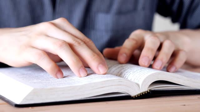 Mann liest Buch durchsuchen, etwas zu finden