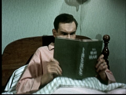 cu, man reading book in bed while frowning - tangled stock videos & royalty-free footage