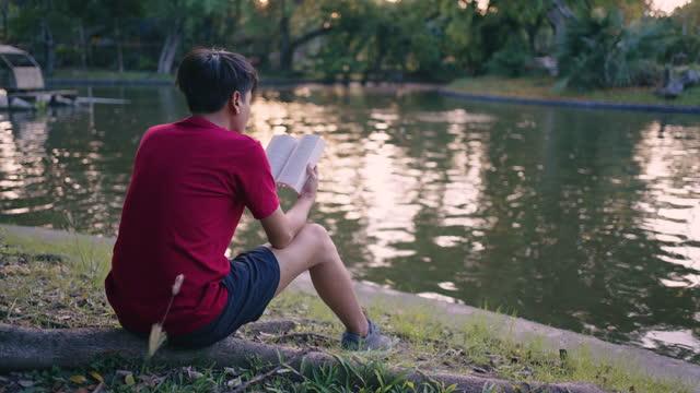 vídeos de stock, filmes e b-roll de homem lendo livro no parque - calções de corrida