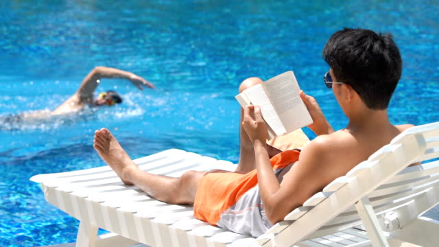 slo mo man reading book near swimming pool in summer - sunbathing stock videos & royalty-free footage