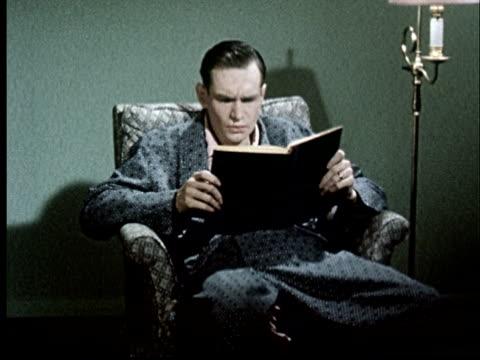 vídeos y material grabado en eventos de stock de ms, man reading book nodding head - sillón