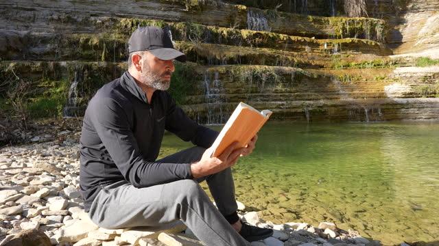 mann lesen buch outdoor-urlaub lifestyle. - 40 44 jahre stock-videos und b-roll-filmmaterial