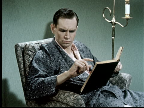 ms, man reading book then preparing to slap flying insect - bathrobe stock videos & royalty-free footage