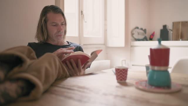 man reading book - tavolo video stock e b–roll