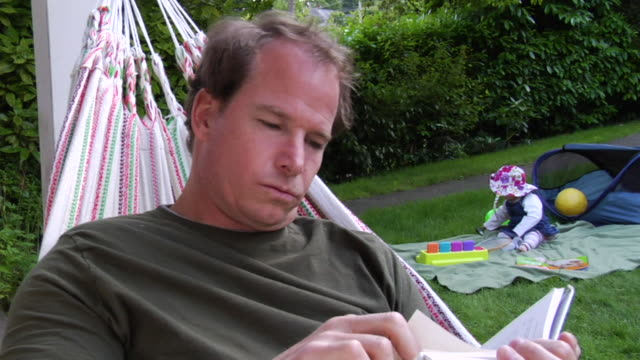 vídeos y material grabado en eventos de stock de ms man reading in hammock as baby plays on blanket in background/ vancouver, bc - kelly mason videos