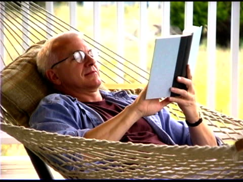 stockvideo's en b-roll-footage met man reading in hammock - achterover leunen