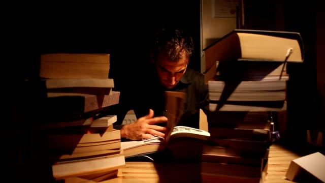 vídeos de stock, filmes e b-roll de homem lendo na biblioteca com livros - cansado
