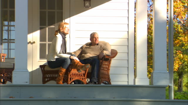 MS Man reading in wicker chair on porch/ Woman arriving and kissing man/ Man and woman walking across lawn/ Livingston, New York