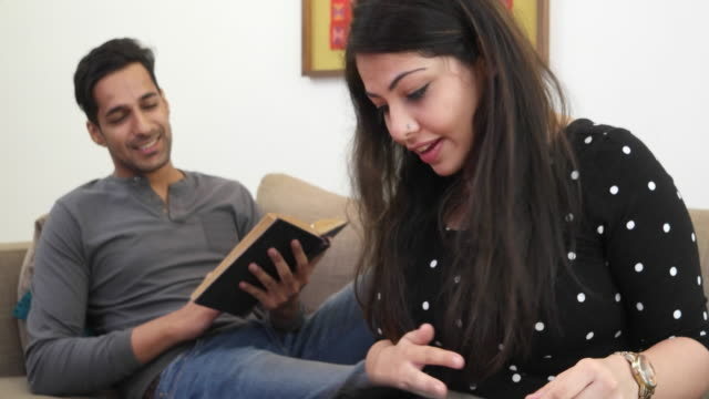 a man reading is joined by her wife, who passes the cellphone to him - giving stock videos & royalty-free footage