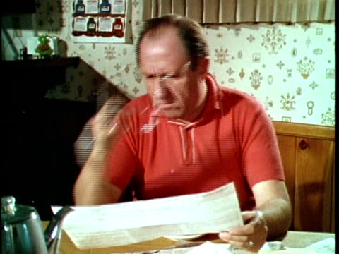 vídeos de stock, filmes e b-roll de 1970 cu montage man reading mail and complaining about property tax rate to wife, los angeles, california, usa, audio - finanças domésticas
