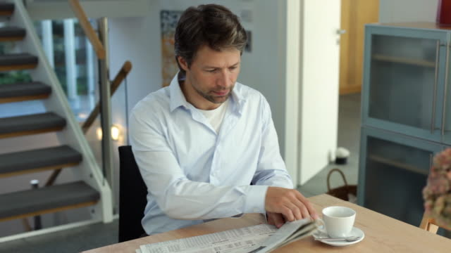 ms man reading newspaper and drinking coffee at table / kleinmachnow, brandenburg, germany - kaffee getränk stock-videos und b-roll-filmmaterial