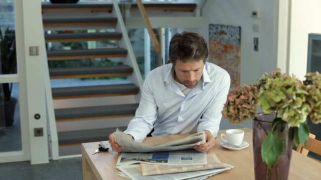 ms man reading newspaper and drinking coffee at table / kleinmachnow, brandenburg, germany - routine stock-videos und b-roll-filmmaterial