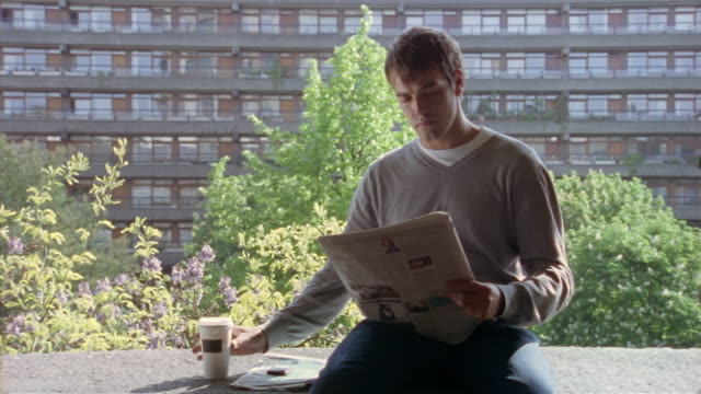 vídeos de stock e filmes b-roll de man reading newspaper and drinking coffee on balcony of high-rise building / london, england - homens de idade mediana