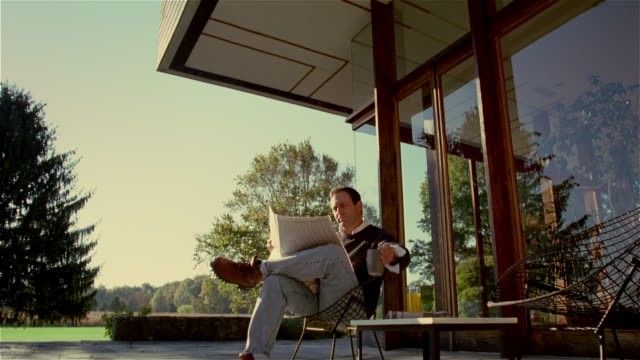 man reading newspaper and drinking coffee on patio in morning - patio stock-videos und b-roll-filmmaterial