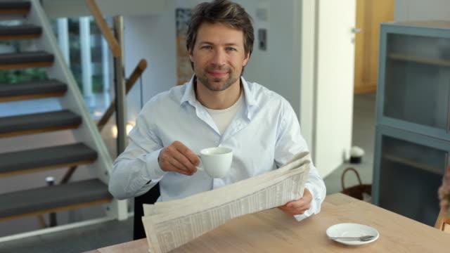 ms man reading newspaper and holding coffee cup / kleinmachnow, brandenburg, germany - sorriso aperto video stock e b–roll
